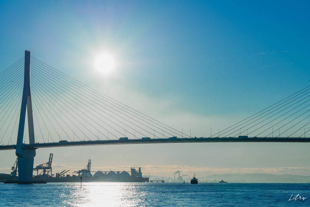 鶴見つばさ橋に昇る朝日と船
