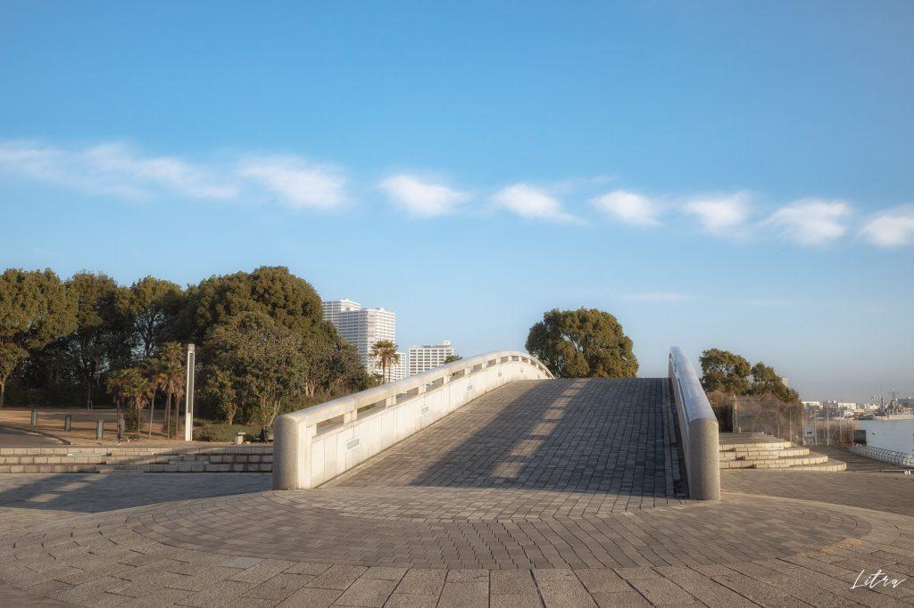 潮入りの池にかかるアーチ橋とかわいい雲
